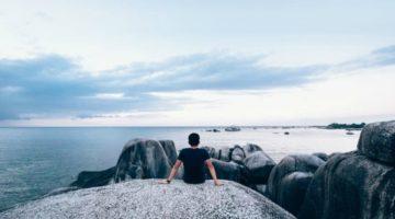 man sitting near rocks on beach