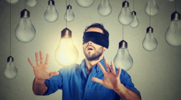 blindfolded man with lightbulbs