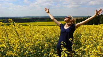 woman holding arms out in field