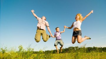 family jumping in a field